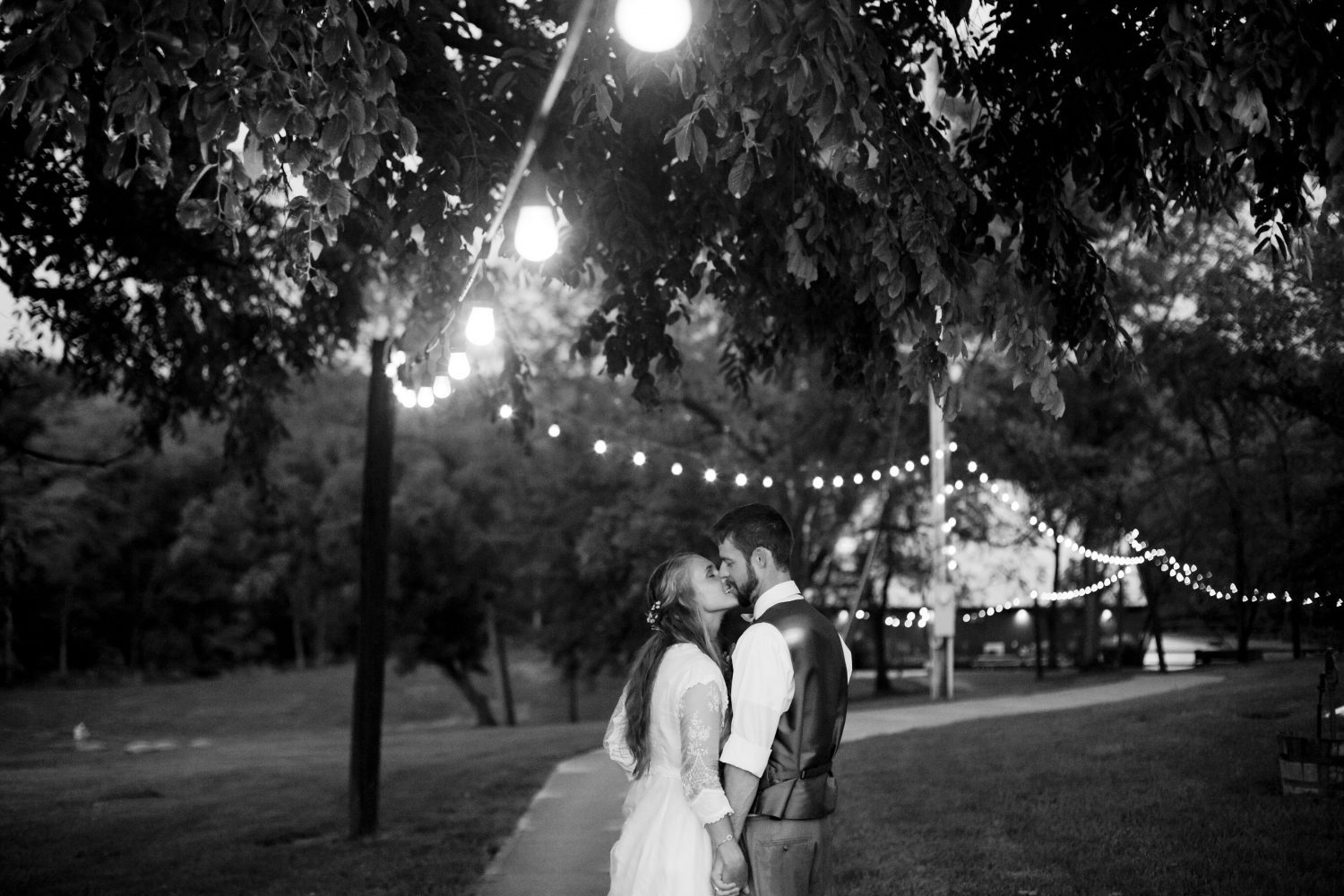 Couple holding hands with backs to the camera and leaning into each other for a kiss. Bistro lights hang overhead among a tree covered path leading to a barn in the background.