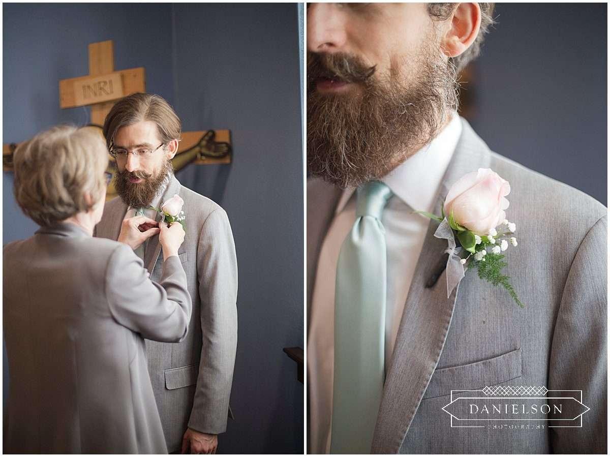 Groom getting corsage pinned on before orthodox wedding ceremony at St. Raphael Orthodox Church in Iowa City, Iowa CIty wedding photographers, cedar rapids wedding photographer