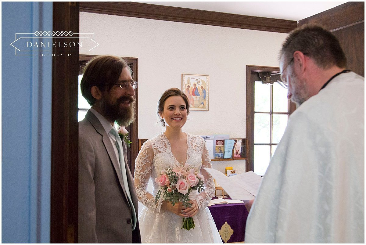 A groom sees his bride for the first time as she rounds the corner before their orthodox wedding ceremony at St. Raphael Orthodox Church in Iowa City, wedding photographer, Iowa City photographer