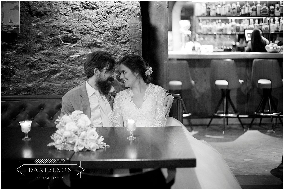 bride and groom sitting in booth at St. Burch Tavern in downtown Iowa City.