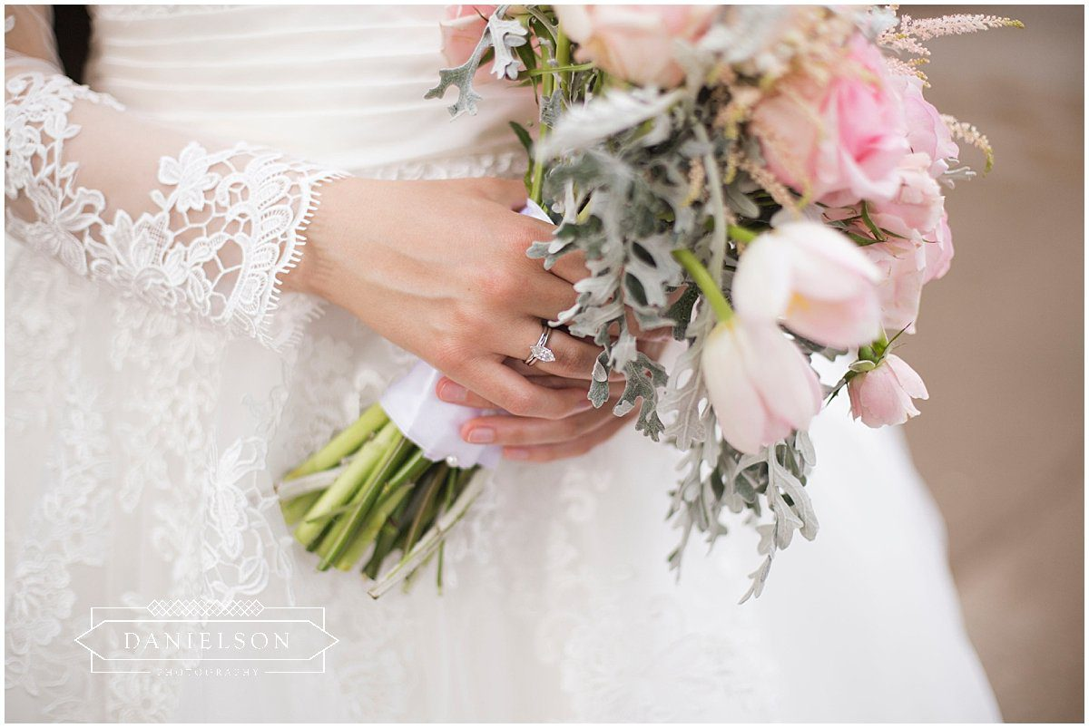 Detail shot of bride holding pink bridal bouquet and her rings.
