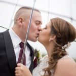 close up of bride and groom kissing in the rain under an umbrella