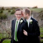 two grooms embrace in the vineyard during sunset at Cedar Ridge Winery