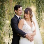 a bride and groom pose for a picture under a willow tree