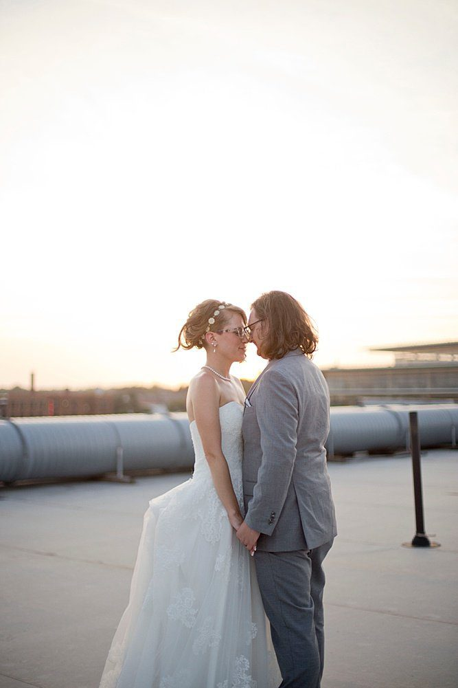 a bride and groom facing each other and holding hands on the rooftop of a building in Des Moines with the sunset glowing around them