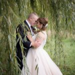 a bride and groom embrace with foreheads touching under a willow tree