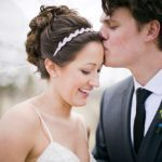 a groom kisses his bride on the forehead as she smiles and her veil billows in the wind