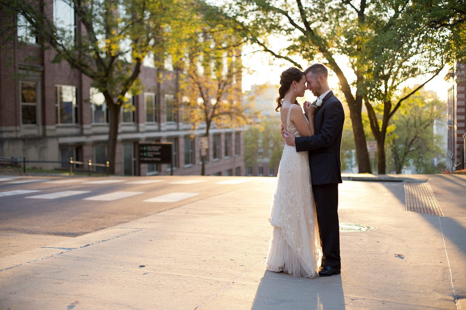 bride and groom facing each other with foreheads touching backlit by a golden sunset standing near the street on the University of Iowa campus