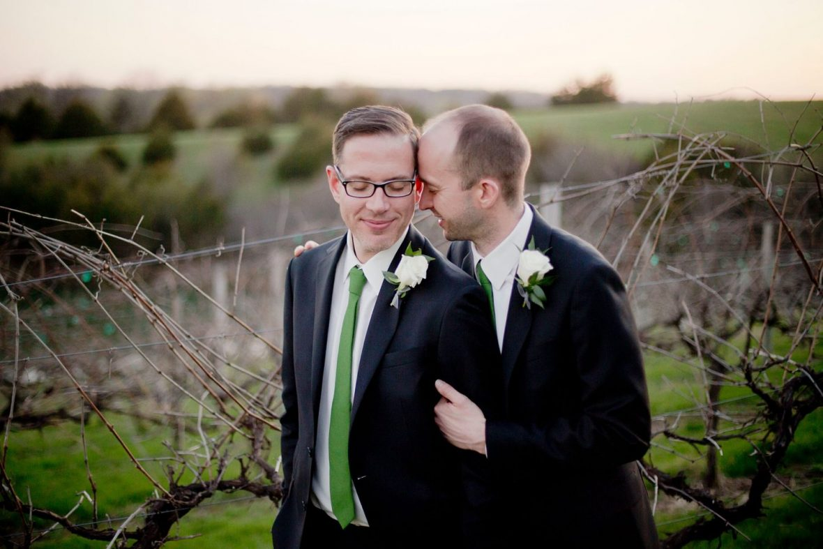 Two men embrace in the rows of a vineyard as the sun sets on their wedding day.