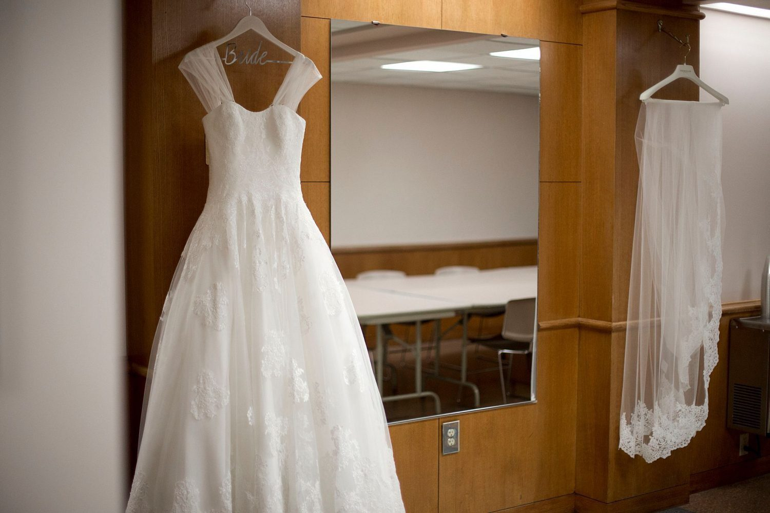 A white wedding gown hangs in the community hall of St. Ambrose Cathedral.