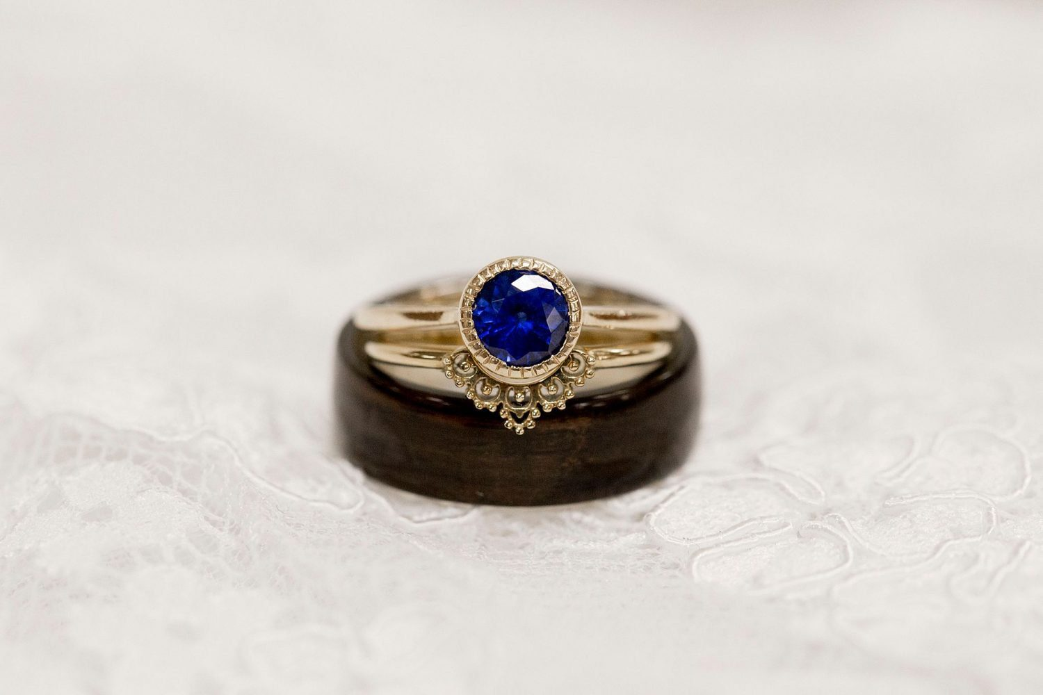 Close up of wedding rings including a vintage blue sapphire engagement ring.