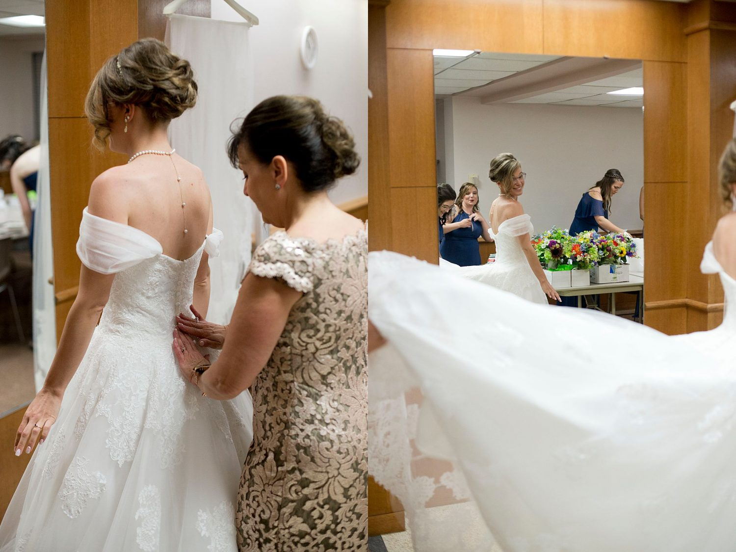 A mother helps the bride get into her wedding gown, the bride admires her reflection in the mirror.