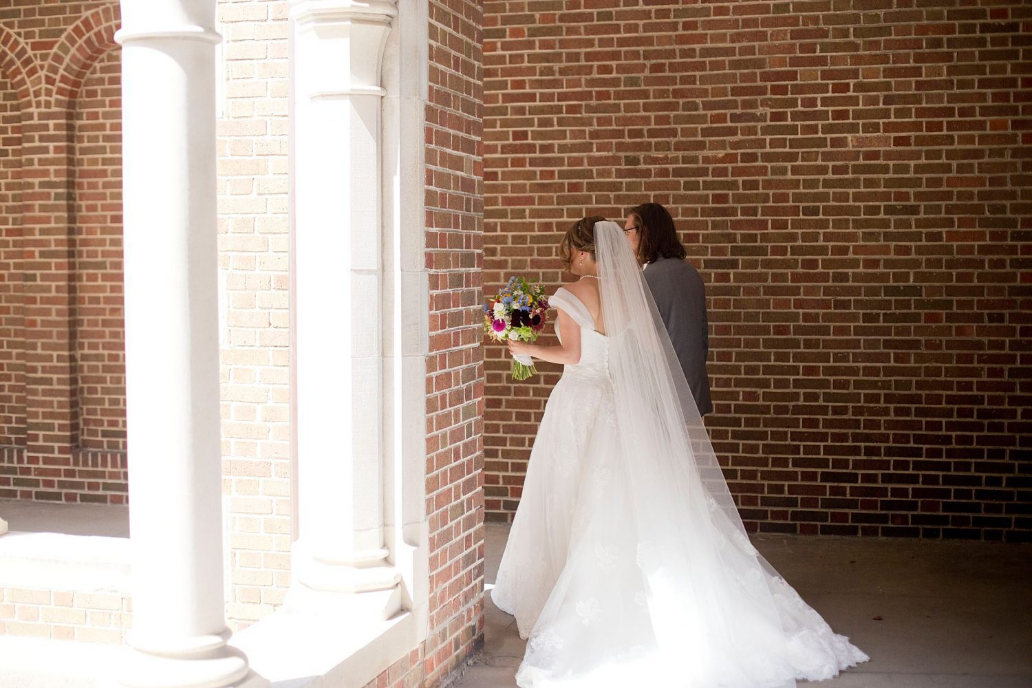 A bride and groom pose for portraits in the courtyard of St Ambrose Cathedral in Des Moines.