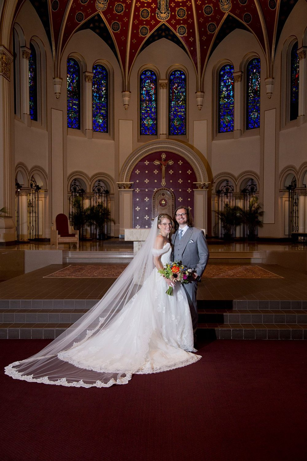 A bride and groom stand in dramatic lighting at the altar of St Ambrose Cathedral in Des Moines.