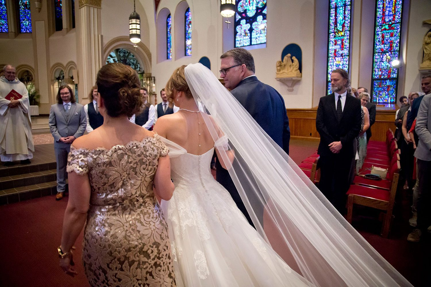 Bride's cathedral length veil trailing behind her at St. Ambrose Cathedral as she is handed off to her groom.