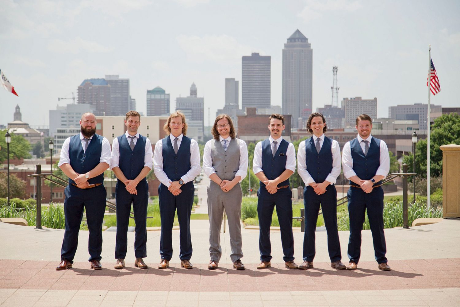 Groomsmen pose at the state capitol building with the skyline of Des Moines behind them.
