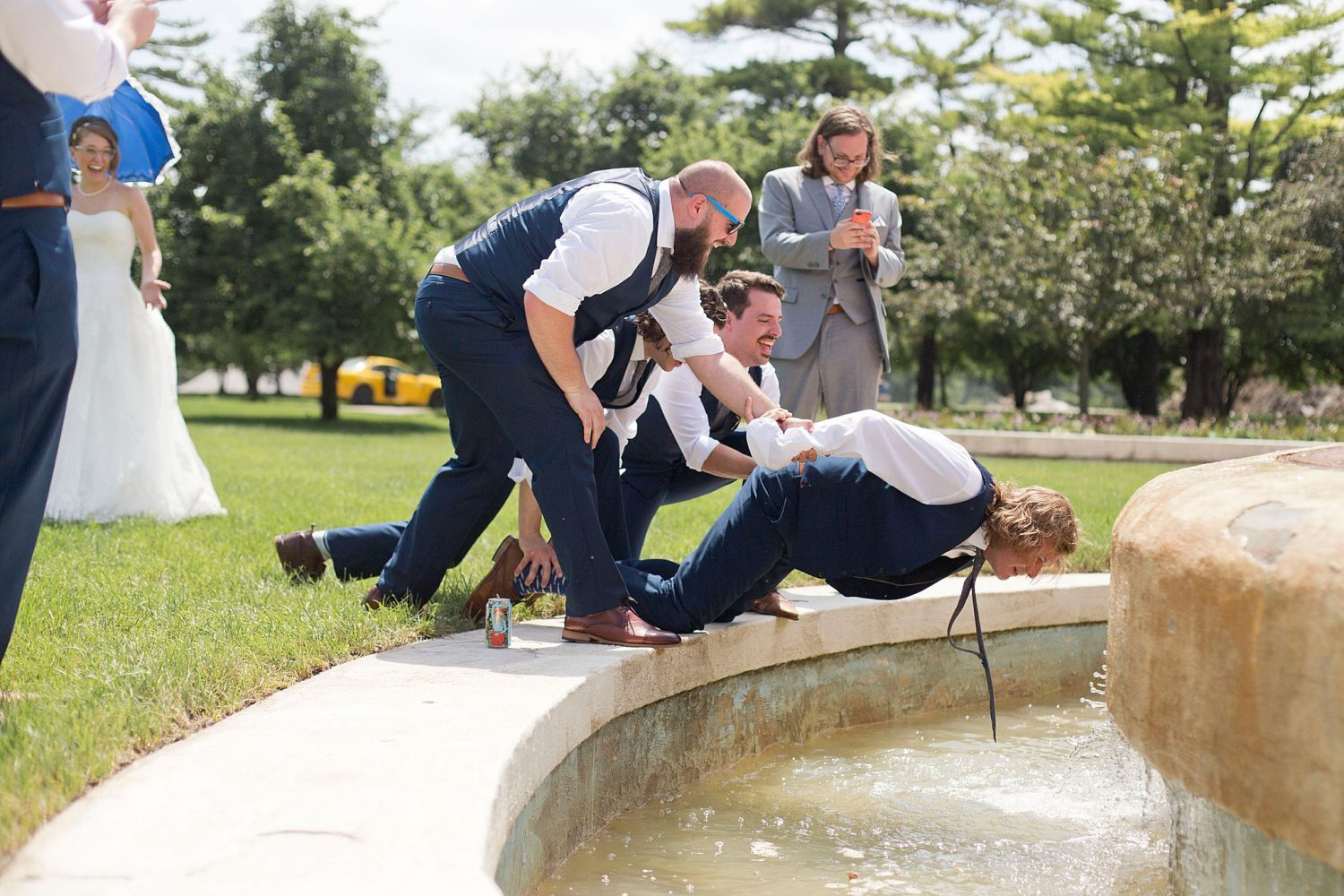 The bridal party cools off in a fountain at Des Moines Waterworks Park.