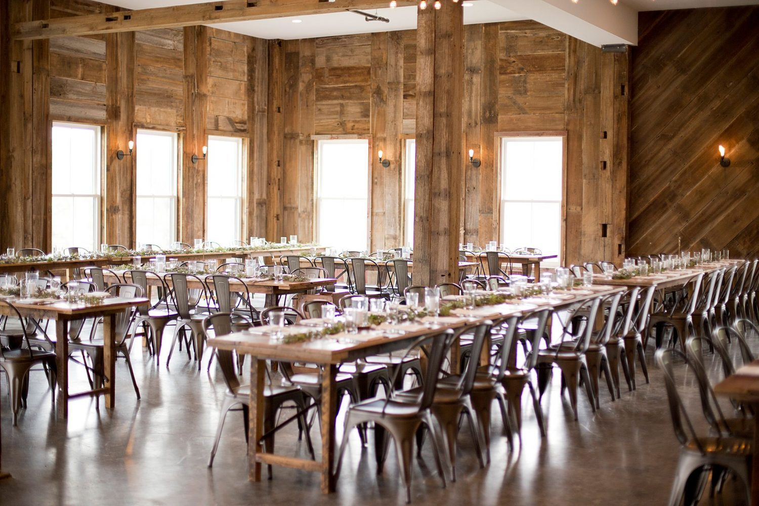A wide shot of the reception venue with metal industrial chairs, farmhouse wood tables, candles, and runners of greenery adorning each table.