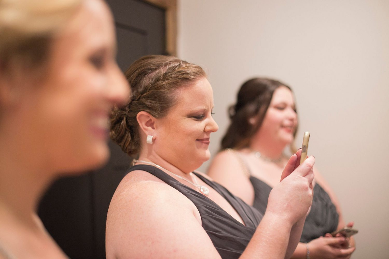 The bride's sister smiling as she watches the bride get ready.