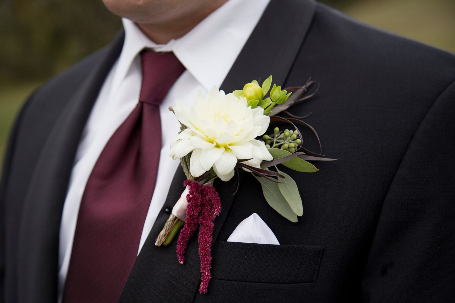 Close up of the groom's burgundy tie and white boutonniere.