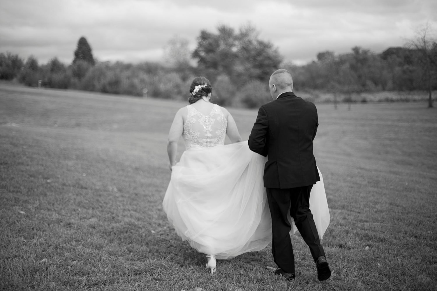 Black and white image of the groom carrying the bride's train as they walk through the grass with their backs to the camera. The orchard is in the background.