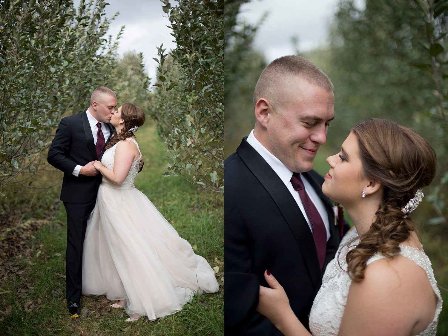 The bride and groom kiss as they stand framed in a row of apple trees.