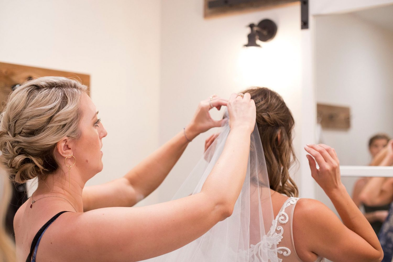 A bridesmaids puts the bride's veil on in the bridal suite of Rapid Creek Cidery