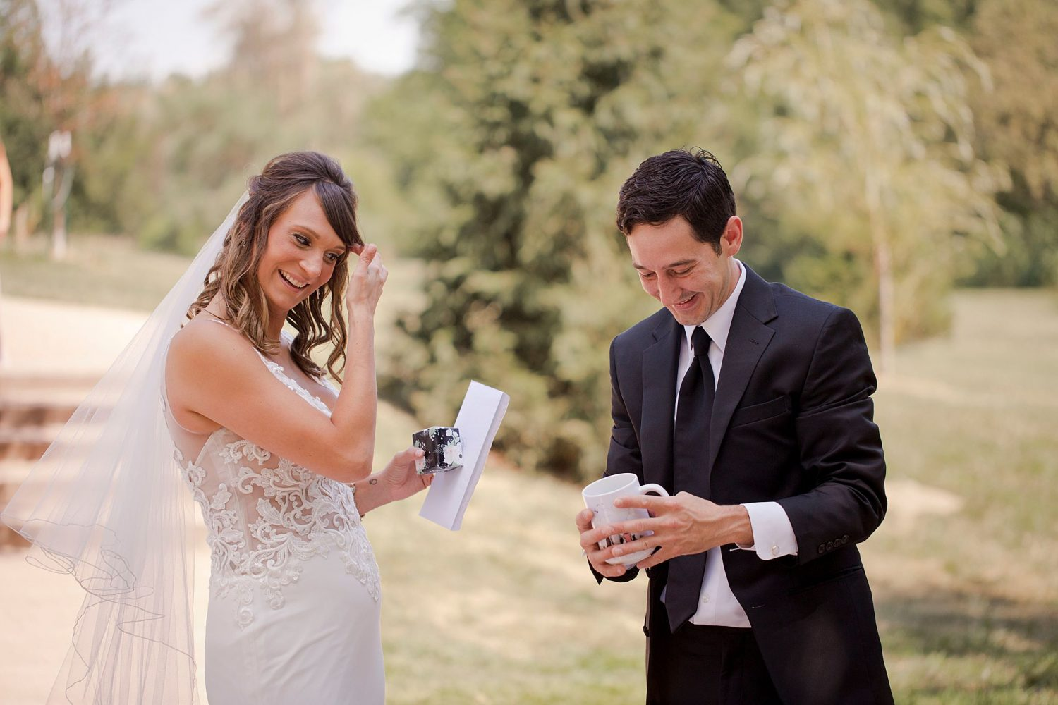 A bride and groom exchange gifts on their wedding day outside at Rapid Creek Cidery.