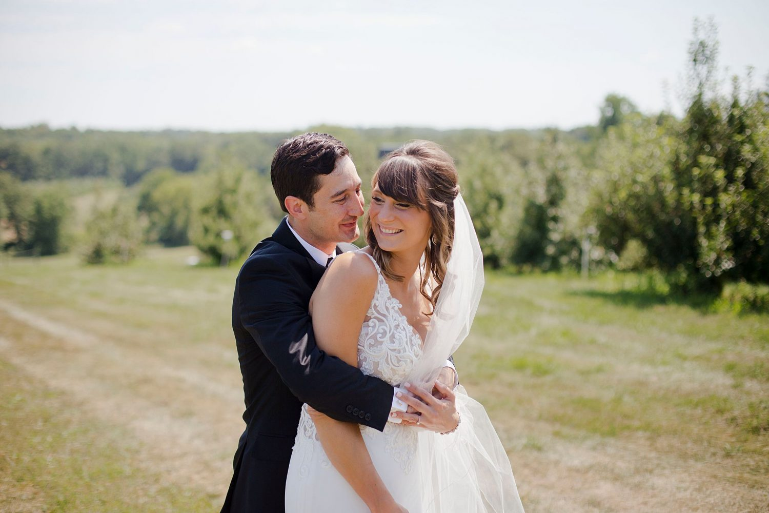 Bride and groom pose together in the orchard on the property of Rapid Creek Cidery in Iowa City.
