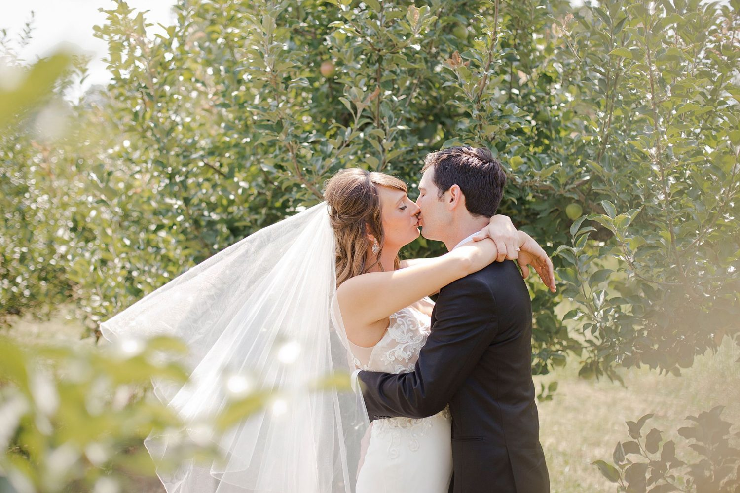 Bride and groom kiss in the orchard on the property of Rapid Creek Cidery.
