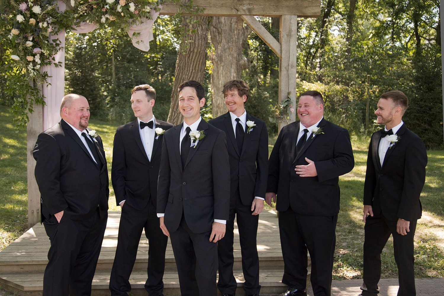 Groom poses with his laughing groomsmen at the outdoor ceremony location of Rapid Creek Cidery.