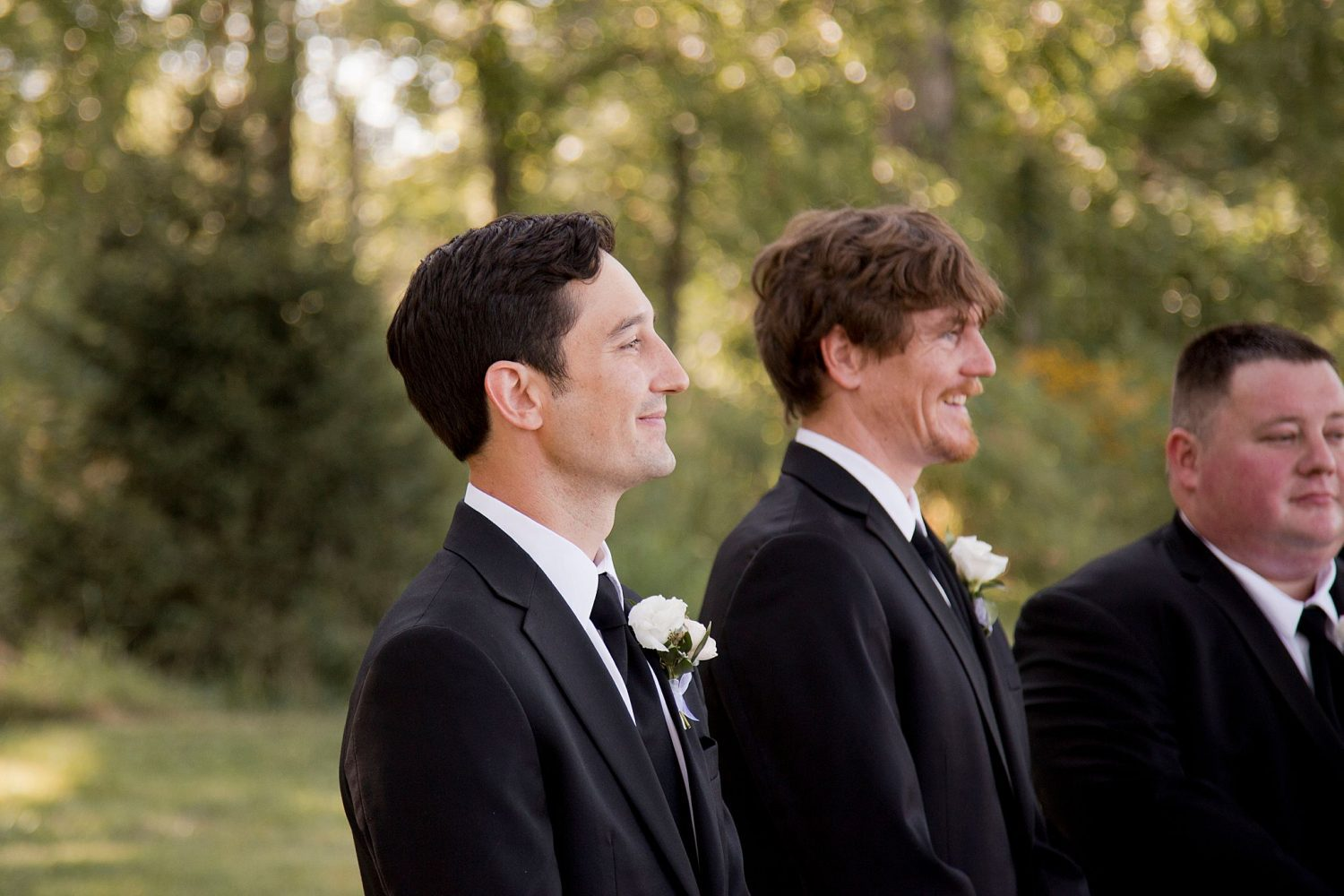 The groom and his brother are seen smiling as they watch his bride walk down the aisle.