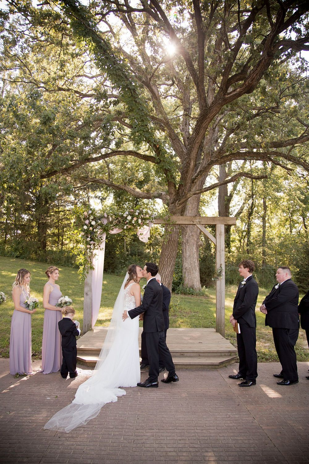 The first kiss under a giant oak tree at the outdoor ceremony site at Rapid Creek Cidery in Iowa City.