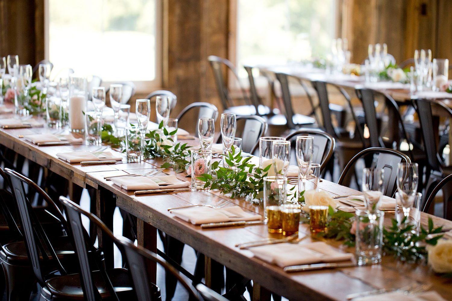Reception table decor of greenery and pale pink flowers by E's Flowers at Rapid Creek Cidery.