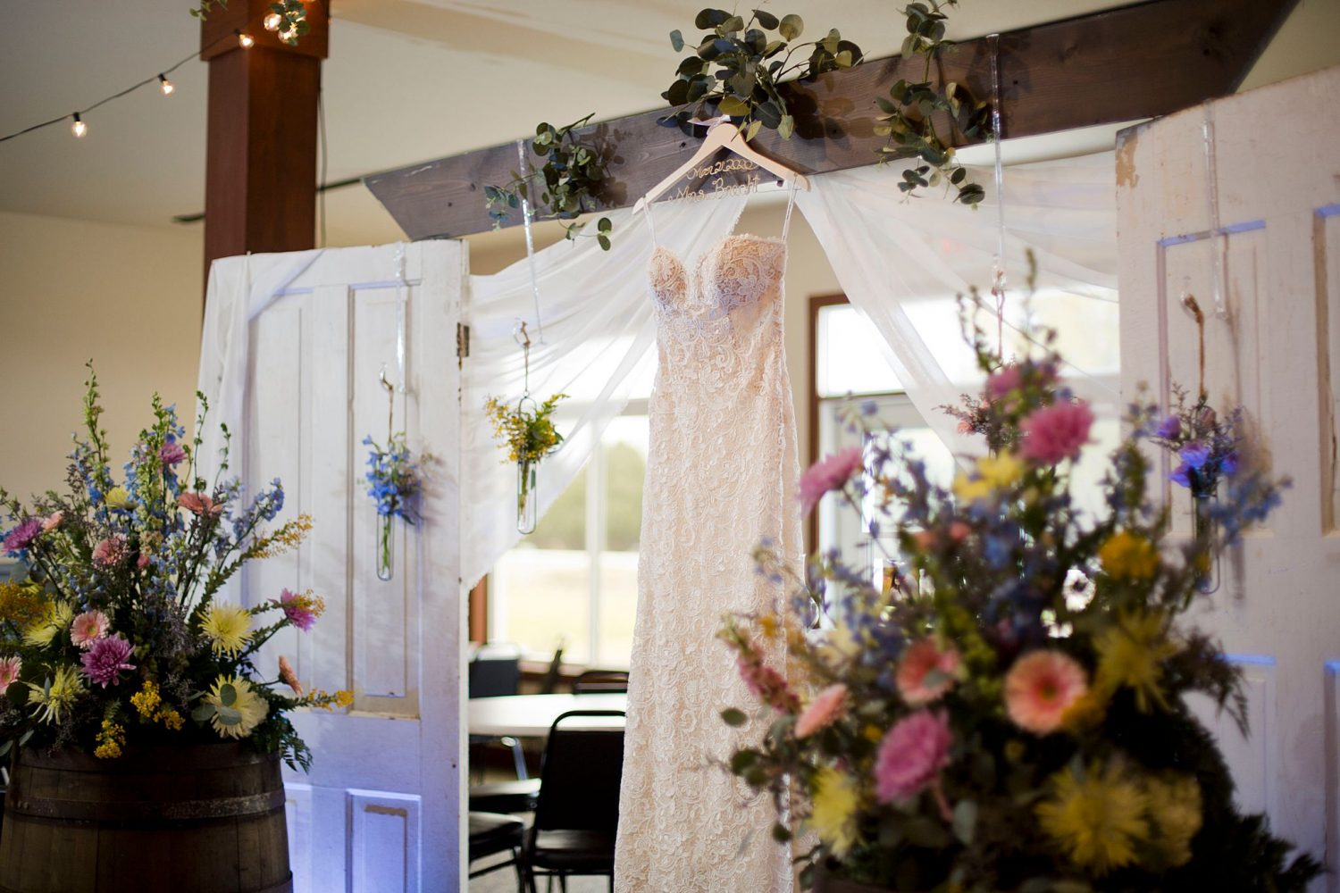 Interior of Lake Macbride golf course decorated for a wedding ceremony with the bridal gown hanging up by the altar.