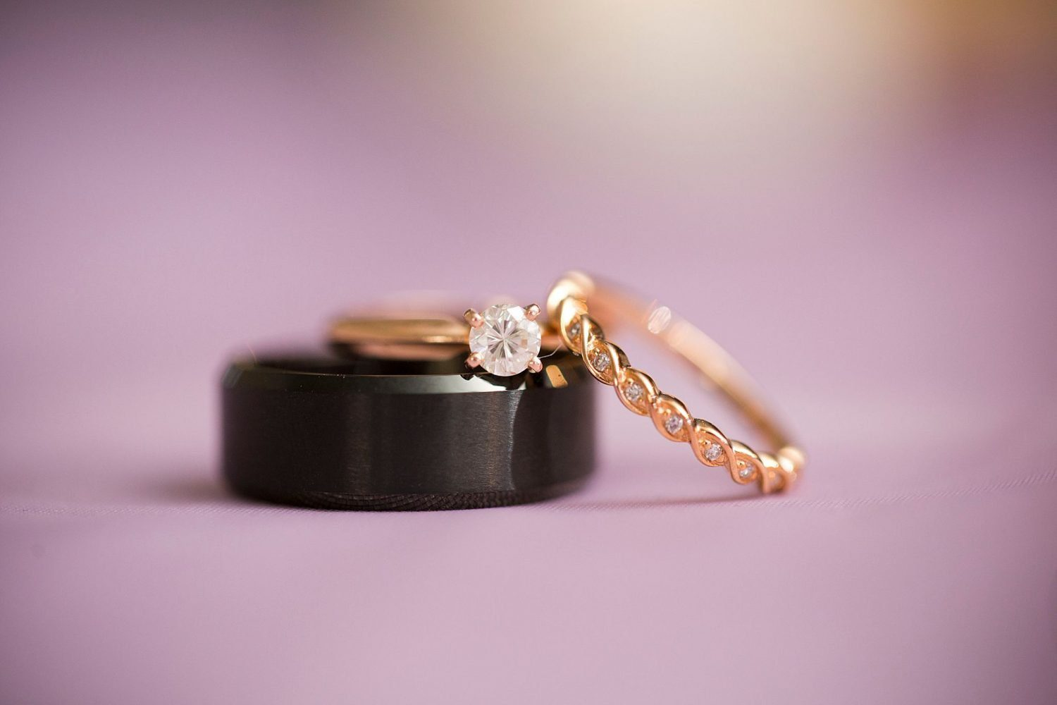 Closeup of groom and bride's wedding rings with a lavender background.