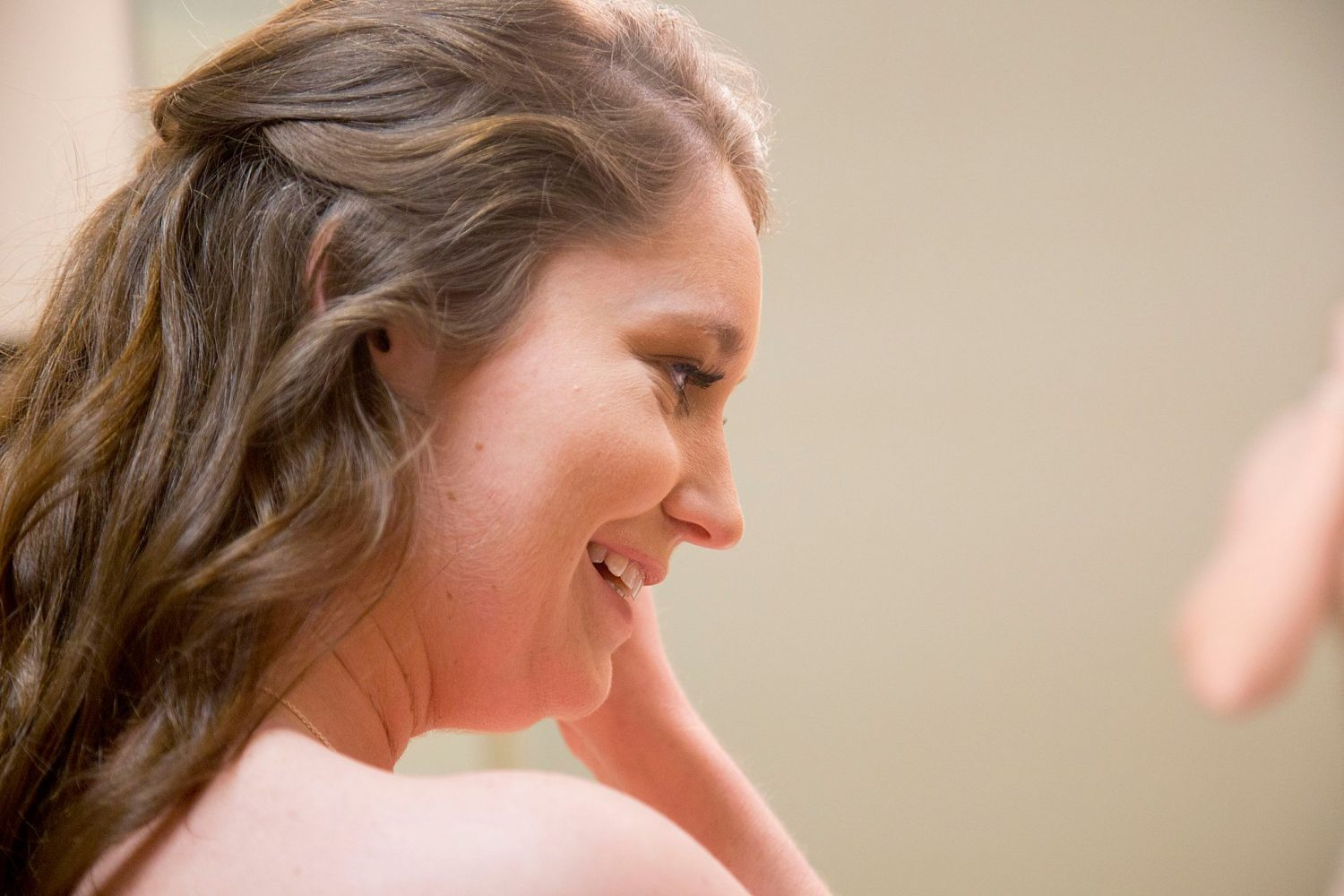 Bride getting ready for her wedding, putting in her earring.