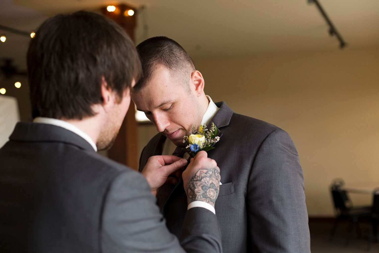 The best man helps the groom with his boutonniere.