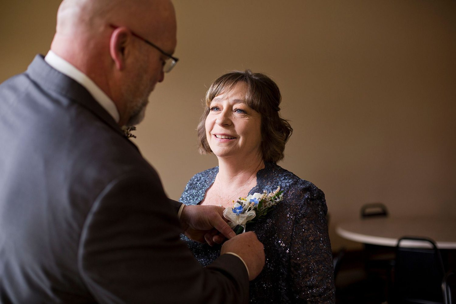 Mother of the bride gets her corsage pinned on by the father of the bride.