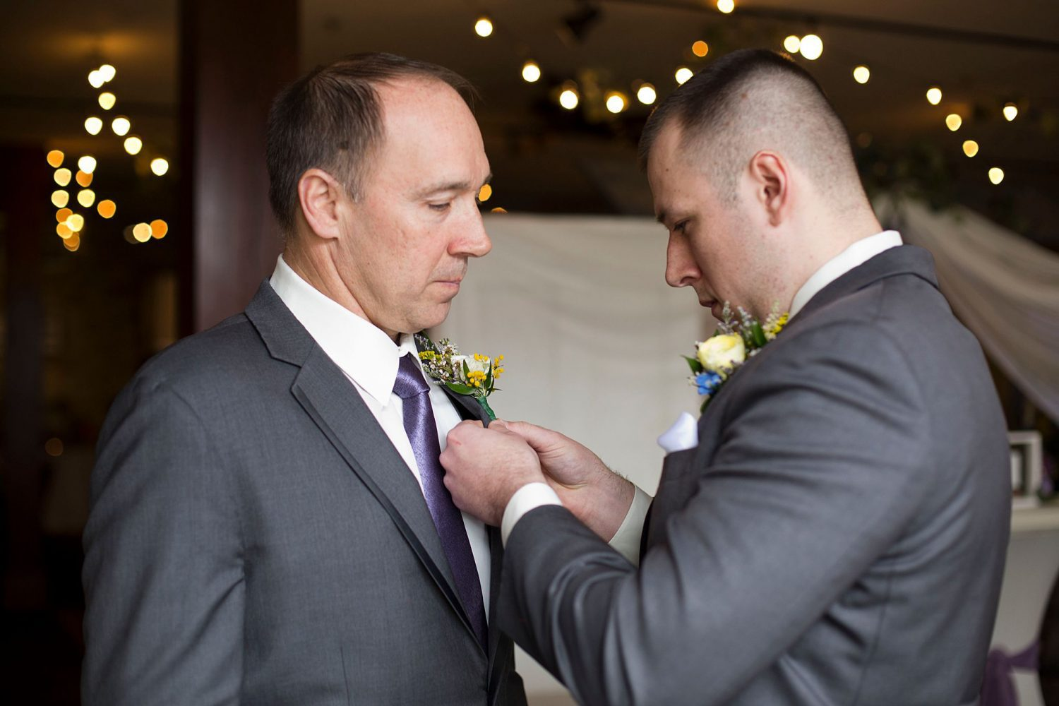 Groom pinning his father's boutonniere on.