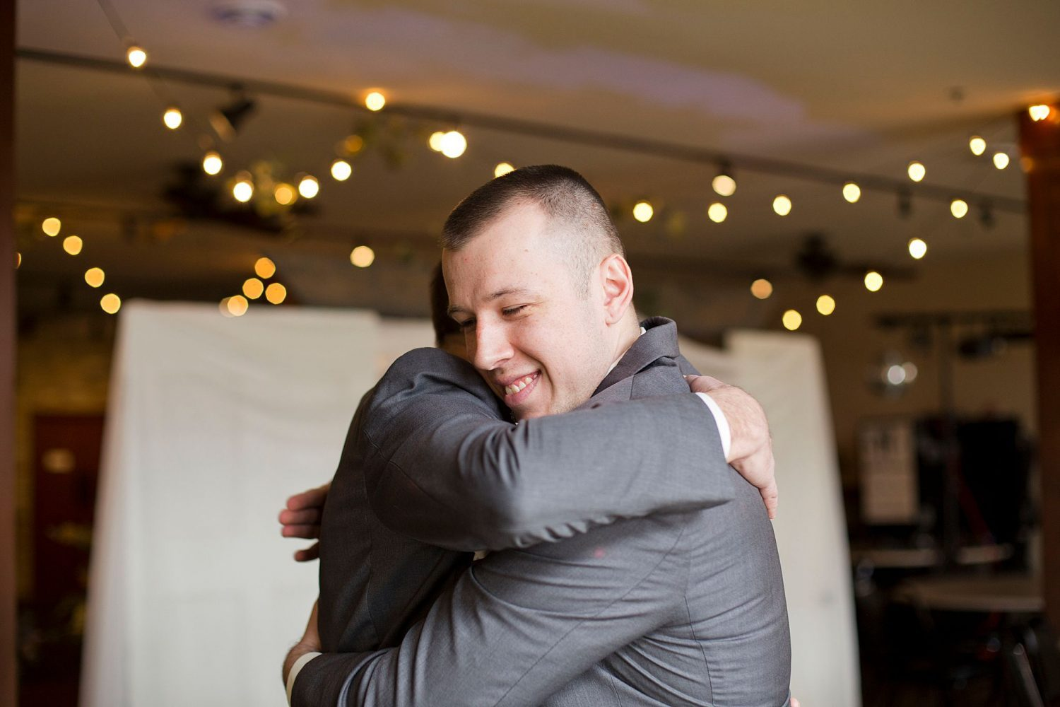 Father and groom give each other a hug.