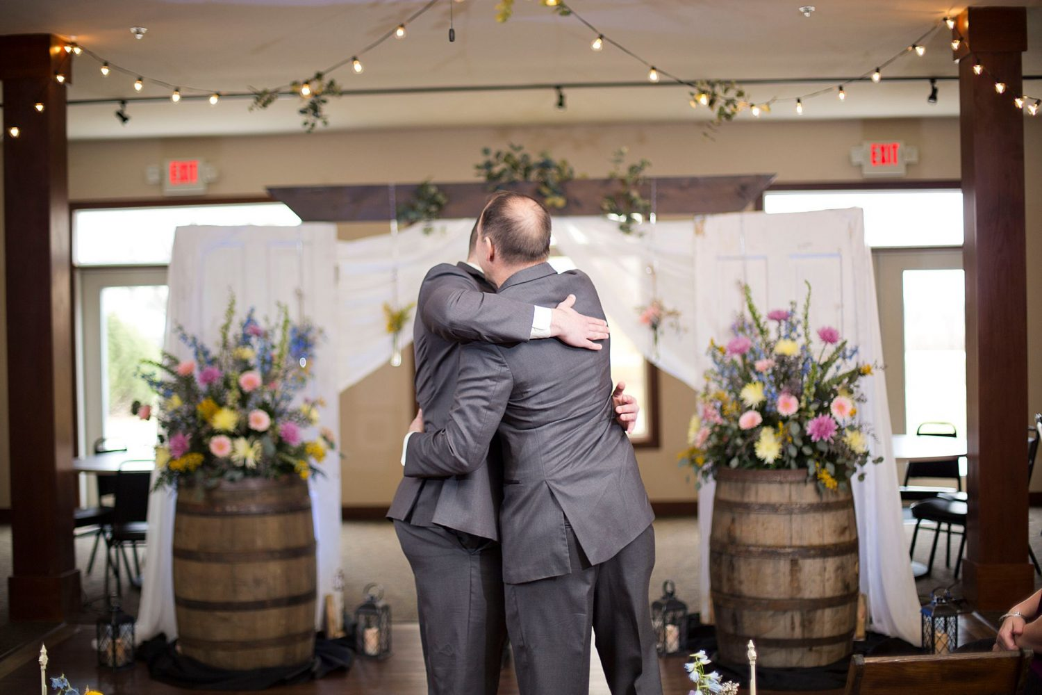 Groom hugs his father after walking down the aisle