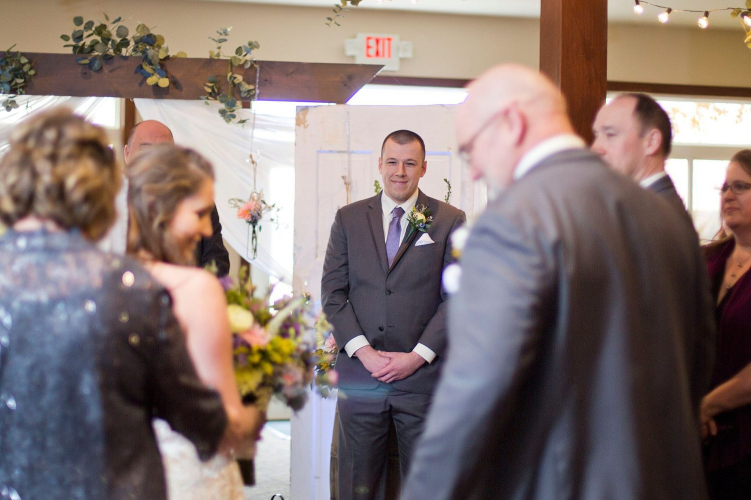 Groom gazes at his bride with a smile as she hugs her parents.