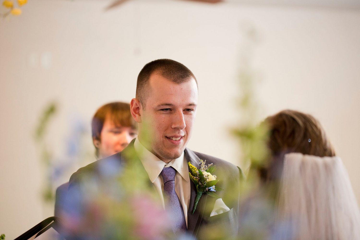 Groom smiles as he says his vows to his bride.
