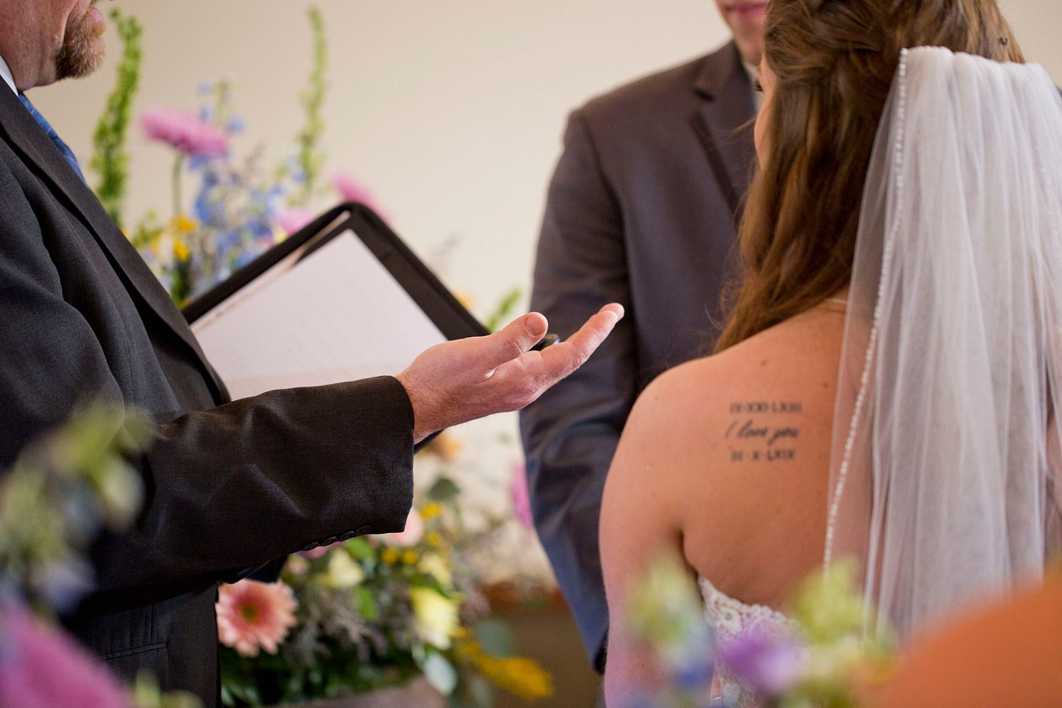 Closeup of officiant's hand holding up the rings.
