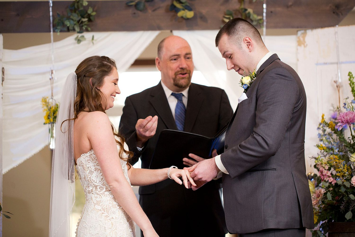 Groom putting ring on bride's finger while they smile.