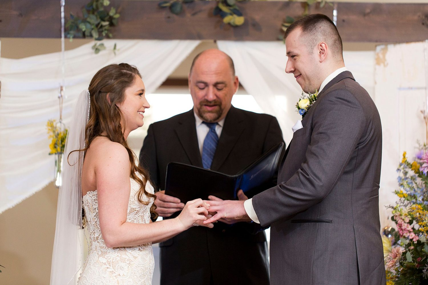 Bride putting ring on groom's finger as they smile.