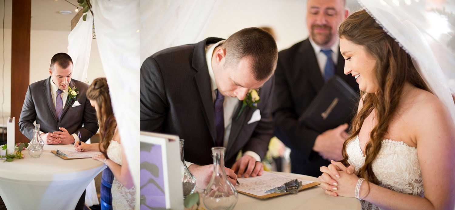 Bride and groom signing marriage certificate.
