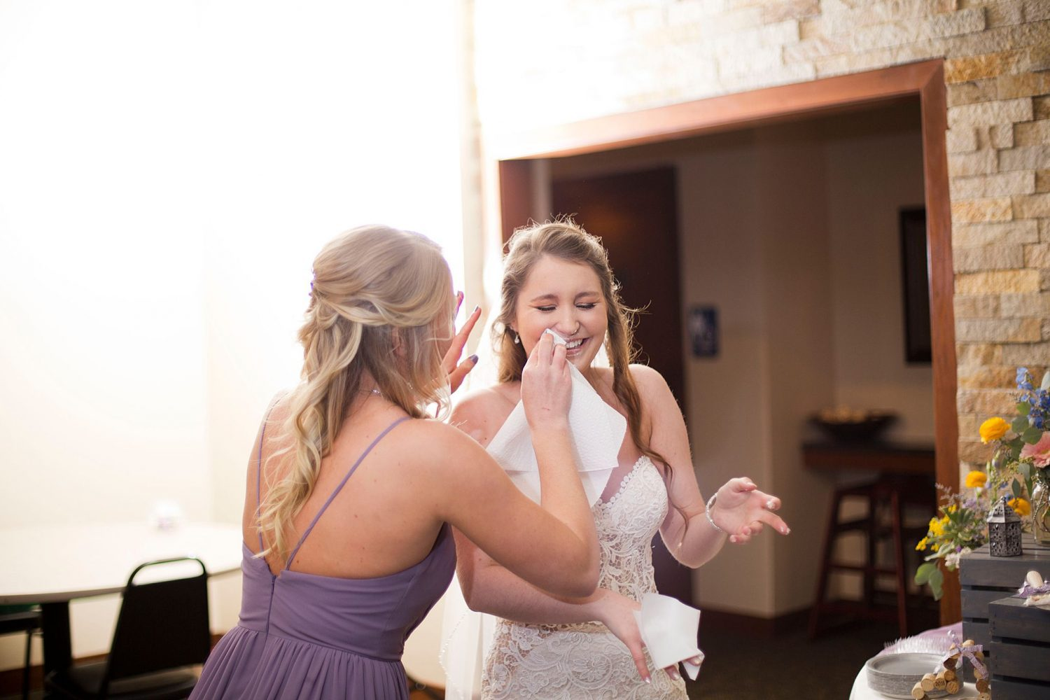 Maid of honor wiping cake of the bride's face.